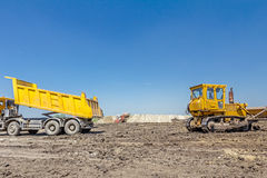 Heavy earthmover is moving earth at building site. Dump truck is. View on heavy bulldozer while he moving, leveling ground at construction site.  Heavy wheels Stock Photos