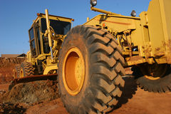 Heavy equipment scraping a road Royalty Free Stock Photos