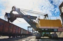 Heavy excavator loading gravel into train for rail freightage Stock Photos
