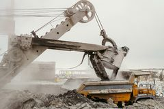 Heavy excavator loads slag into a big mining dump truck. Work in heavy industry Stock Images