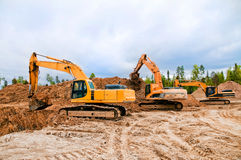 Heavy excavators. Three excavators working on a construction site Royalty Free Stock Photography