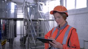 Heavy female work, portrait of engineer girl into helmet and coveralls with tablet laptop making calculated decisions