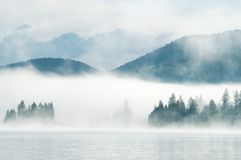 Heavy fog in the early morning on a mountain lake Royalty Free Stock Photo