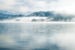Heavy fog in the early morning on a mountain lake Stock Photos