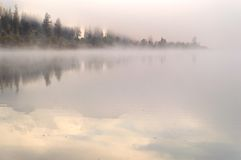 Heavy fog in the early morning on a mountain lake Stock Photo