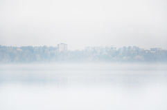 Heavy fog on the lake Senezh in Solnechnogorsk fall in calm weather. View of the residential high-rise buildings through the haze. Autumn morning water Stock Image