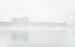 Heavy fog on the lake Senezh in Solnechnogorsk fall in calm weather. View of the residential high-rise buildings through the haze. Autumn morning water Royalty Free Stock Image