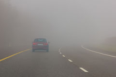 Heavy fog in the motorway. Danger. Driving a car in the motorway with low visibility due to foggy conditions royalty free stock photography