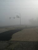 Heavy fog and traffic lights with patched roads, vertical image Stock Photo