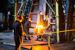 Heavy forgings Plant. Worker puts the billet under the press Stock Photos