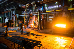 Heavy forgings Plant. Workers carry a workpiece from the furnace to the hammer Royalty Free Stock Photos