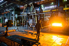 Heavy forgings Plant. Workers carry a workpiece from the furnace to the hammer Stock Photography