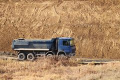 A heavy four-axle dump truck of blue drives along a dirt road against the background of a clay embankment. Career and road works. Driver`s profession stock photography