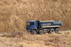 A heavy four-axle dump truck of blue drives along a dirt road against the background of a clay embankment. Career and road works. Driver`s profession royalty free stock images