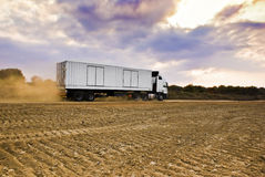 Heavy Goods in Transit via Dirt Roads - Rear View Stock Images