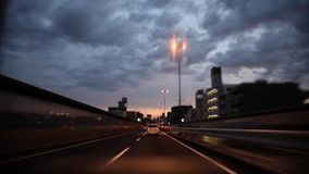 Heavy gray rain cloud in sky over busy traffic highway road in first person pov on stunning view from wind shield glass. First person pov on stunning view from stock footage