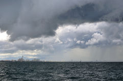 Heavy gray rain clouds happen in the city near sea Stock Images