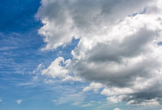 Heavy grey cloud on a blue summer sky Stock Image