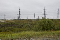 Heavy grey clouds in the cold autumn sky over green fields, trees, forests, streams. Before storm. Electric poles.  Stock Photography