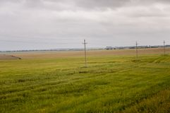 Heavy grey clouds in the cold autumn sky over green fields, trees, forests, streams. Before storm. Electric poles.  Royalty Free Stock Photography