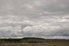 Heavy grey clouds in the cold autumn sky over rivers, fields, forests and mountains.  Stock Photo