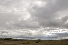 Heavy grey clouds in the cold autumn sky over rivers, fields, forests and mountains.  Royalty Free Stock Photo