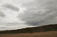Heavy grey clouds in the cold autumn sky over rivers, fields, forests and mountains.  Stock Photos