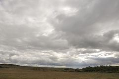 Heavy grey clouds in the cold autumn sky over rivers, fields, forests and mountains.  Stock Images