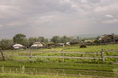 Heavy grey clouds in the cold autumn sky over  village with small houses far away in the mountains and fields. Travelling on the s. Uburb roads. People living Stock Photography