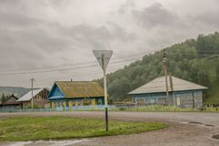 Heavy grey clouds in the cold autumn sky over  village with small houses far away in the mountains and fields. Travelling on the s. Uburb roads. People living Stock Photos
