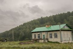 Heavy grey clouds in the cold autumn sky over  village with small houses far away in the mountains and fields. Travelling on the s. Uburb roads. People living Royalty Free Stock Photos