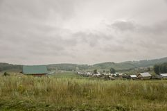Heavy grey clouds in the cold autumn sky over  village with small houses far away in the mountains and fields. Travelling on the s. Uburb roads. People living Stock Image