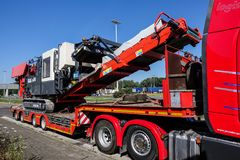 Heavy hauling, mobile jaw crusher. AACHEN, NRW, GERMANY - JUNE 30, 2018: Heavy hauling of a mobile jaw crusher, transported on a special low-loader trailer royalty free stock photos
