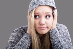 Heavy headache. A portrait of a pretty caucasian girl wearing a hooded jersey holding her head in her hands a pulling a face in discomfort Royalty Free Stock Photo