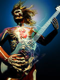 Heavy heart. Guitarist seen in transparency, with his skeleton and his heart throwing flashes of lightning whereas he plays his music Royalty Free Stock Photo