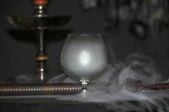 Heavy hookah smoke under a brandy glass on a gray background, hookah tube Royalty Free Stock Photos