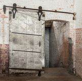 Sliding heavy industrial metal door in old warehouse. Heavy industrial door in doorway against distressed brick wall in old warehouse Royalty Free Stock Images
