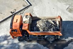 Heavy industrial dump truck .City road construction and renewal site. Dump truck brought in to repair roads and sidewalks. Replacing curbs on the roads. Almaty stock photo