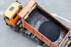 Heavy industrial dump truck unloading hot asphalt .City road construction and renewal site.  stock photography