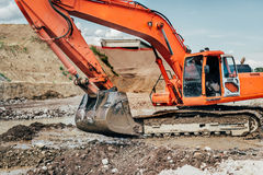 Heavy industrial excavator working during earthmoving works at highway construction site Stock Photos