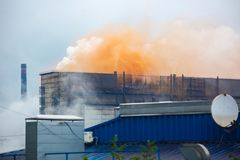 Heavy industrial iron plant emissions into the atmosphere , clouds of orange smoke from old iron factory. A lot of smoke from the metallurgical plant stock photos