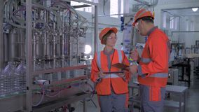 Heavy industry, happy female and male factory workers in helmets with computer tablet in hand near automatic belt line