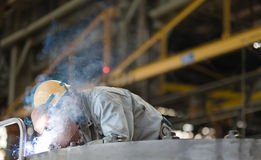 Heavy industry manual worker welding/grinding in a Stock Images