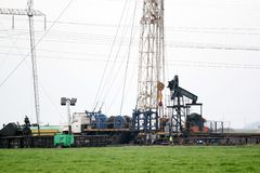 Oilfield with rig and pump jack Royalty Free Stock Photo
