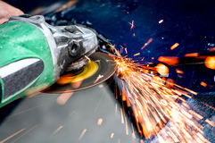 Heavy industry worker cutting steel with angle grinder. In workshop, at car service Stock Photo