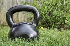 Heavy iron  kettlebell in backyard Royalty Free Stock Photos