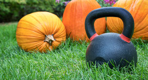 Heavy kettlebell and pumpkins Stock Photo