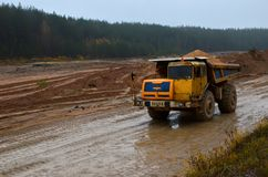 Heavy large quarry dump truck. The work of construction equipment in the mining industry. Production useful minerals. Sand transportation stock images