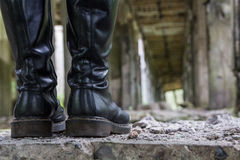 Heavy leather boots. Black hiking boots in an abandoned concrete factory from the period of World War 2 in Poland royalty free stock image