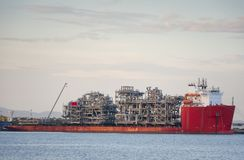 Heavy lift cargo ship barge transporting an oil rig Platform. To installation at sea stock photography